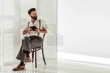 handsome bearded man sitting on chair and holding vintage film camera