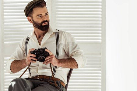 Photo for Handsome bearded man sitting on chair and holding vintage film camera - Royalty Free Image
