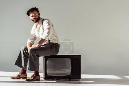 Photo pour Bel homme barbu assis sur tv vintage et regardant la caméra sur fond gris - image libre de droit
