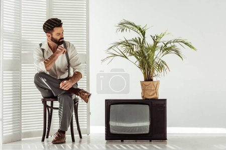 Photo for Handsome bearded man sitting on chair near room divider and retro tv and looking at plant in pot - Royalty Free Image