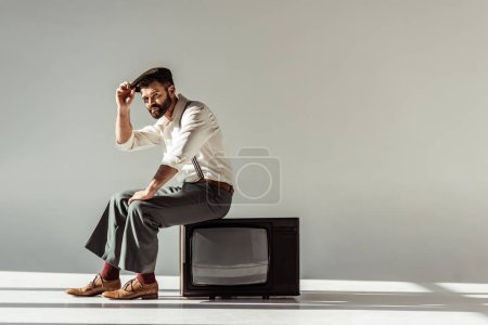 Photo pour Bel homme barbu assis sur vintage tv, toucher le chapeau sur la tête et regardant la caméra sur fond gris - image libre de droit
