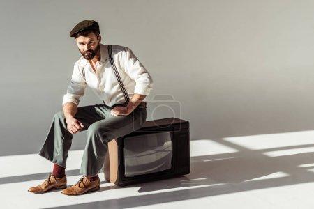 Photo pour Bel homme barbu élégant assis sur vintage tv et regarder la caméra - image libre de droit