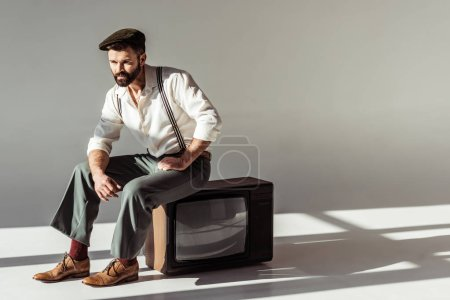 Photo for Handsome stylish bearded man in cap sitting on vintage tv on grey background - Royalty Free Image