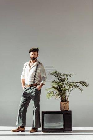 Photo pour Beau barbu homme en cap se tenant près vintage tv avec la plante en pot et en regardant la caméra - image libre de droit