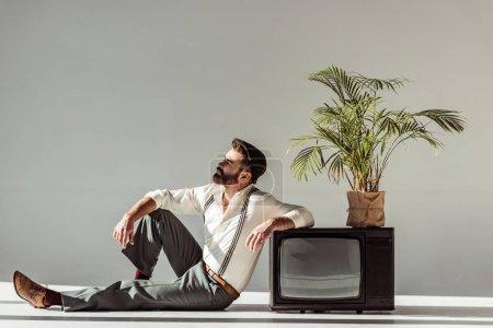 Photo pour Bel homme barbu assis sur le sol près de la télévision vintage avec plante en pot - image libre de droit