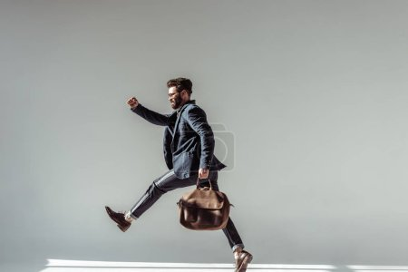 bearded man with brown bag jumping on grey background