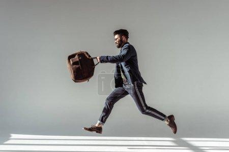 Foto de Hombre barbudo guapo con bolsa marrón saltando sobre fondo gris - Imagen libre de derechos