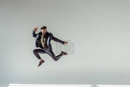 Photo pour Homme barbu, chapeau et lunettes de sauter haut sur fond gris - image libre de droit