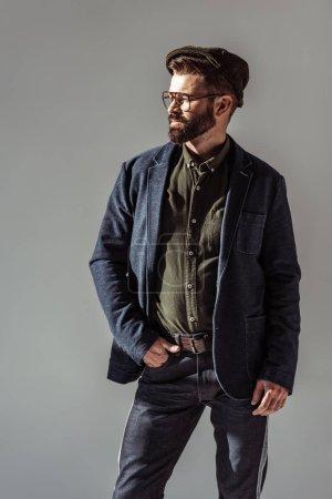 Foto de Hombre guapo con barba con la mano en el bolsillo aislado en gris - Imagen libre de derechos