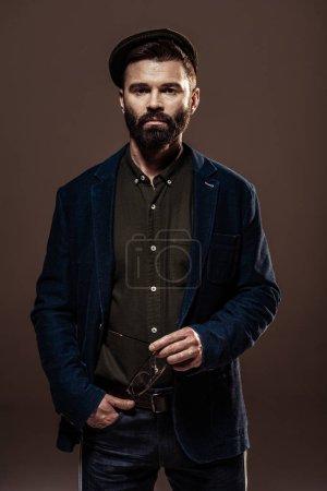 Foto de Guapo hombre con barba con la mano en el bolsillo Copa y mirando a cámara aislada en marrón - Imagen libre de derechos