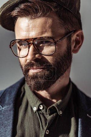 Foto de Cerrar vista de guapo barba en gafas y gorra mirando a cámara aislada en gris - Imagen libre de derechos