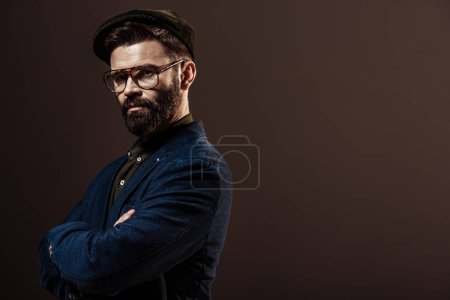Photo for Handsome bearded man with arms crossed looking at camera isolated on brown - Royalty Free Image