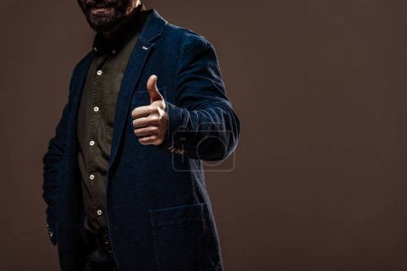 Photo for Cropped view of man showing thumb up isolated on brown - Royalty Free Image