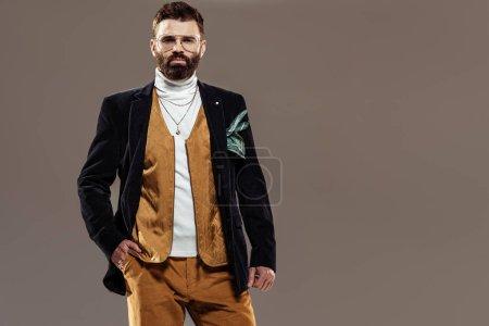 Photo pour Bel homme barbu à lunettes main dans la poche en regardant la caméra isolée sur brown - image libre de droit