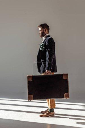 Foto de Vista lateral del guapo hombre barbudo en vasos con maleta vintage - Imagen libre de derechos
