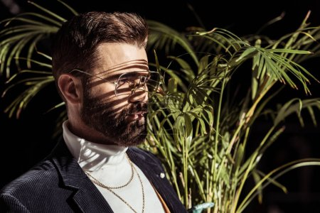 Photo for Handsome bearded man in glasses with green houseplant isolated on black - Royalty Free Image