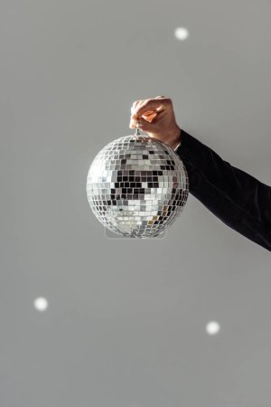 Photo for Cropped view of man holding disco ball on grey background - Royalty Free Image