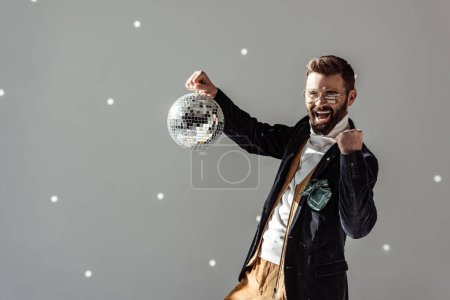 cheerful man in glasses holding disco ball and looking at camera on grey background