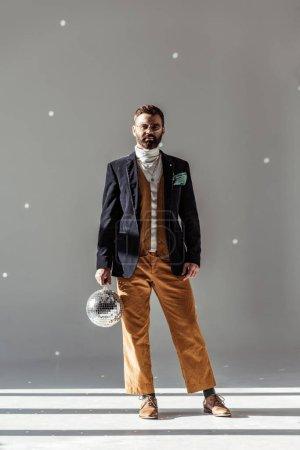 Photo pour Homme barbu debout, tenant une boule disco et regardant la caméra sur fond gris - image libre de droit