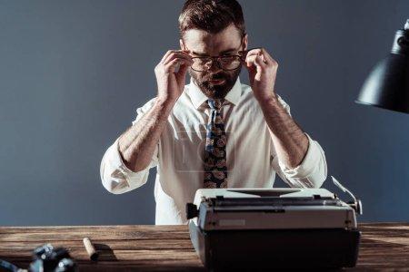 Foto de Periodista barbudo sentado en mesa con máquina de escribir, tocar las gafas y mirando a cámara en fondo gris - Imagen libre de derechos