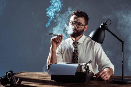 Photo pour Gentil journaliste barbu assis à table avec la machine à écrire et à fumer sur fond gris - image libre de droit