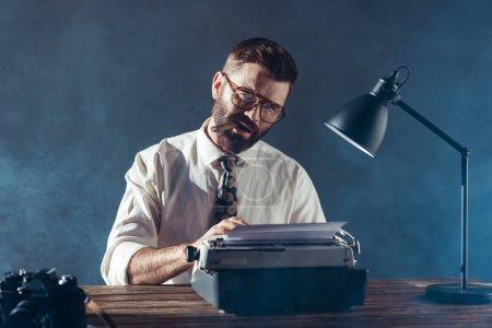 Photo pour Journaliste barbu assis à table, tapant sur des machines à écrire, fumant et regardant la caméra sur fond gris - image libre de droit
