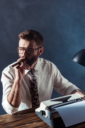 Photo for Thoughtful bearded journalist sitting at table with retro typewriter and smoking on grey background - Royalty Free Image
