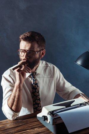Photo pour Gentil journaliste barbu assis à table avec la machine à écrire rétro et fumer sur fond gris - image libre de droit