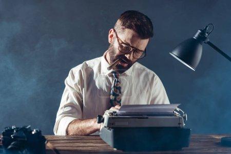 Photo pour Journaliste barbue assis à table, en tapant sur la machine à écrire vintage et fumer sur fond gris - image libre de droit
