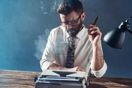 handsome journalist in glasses sitting at table, looking on vintage typewriter and smoking on grey background