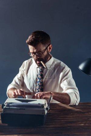 Foto de Guapa periodista en gafas sentado en la mesa, escribiendo en máquina de escribir vintage y fumar en fondo gris - Imagen libre de derechos