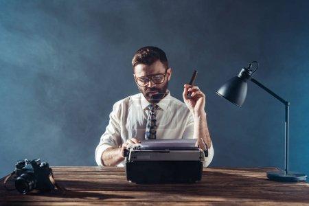 Photo pour Beau journaliste dans des verres assis à table avec la machine à écrire rétro et fumer sur fond gris - image libre de droit