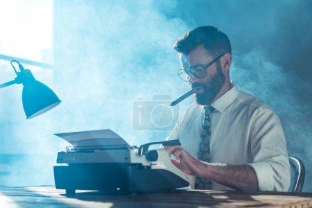 Foto de Periodista de barba en gafas sentado en la mesa, escribiendo en máquina de escribir vintage y fumar junto a la ventana - Imagen libre de derechos