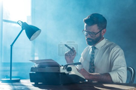 Photo for Bearded journalist in glasses sitting at table, holding cigar and looking at vintage typewriter near window - Royalty Free Image