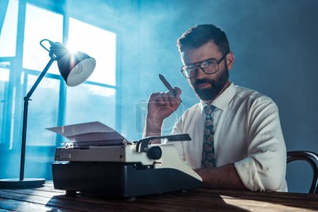 Photo for Bearded journalist in glasses sitting at table with vintage typewriter, holding cigar and looking at camera near window - Royalty Free Image