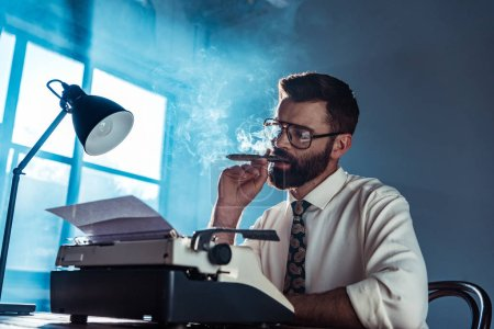 Foto de Periodista guapo pensativo sentado en la mesa, mirando a la máquina de escribir vintage y fumar junto a la ventana - Imagen libre de derechos