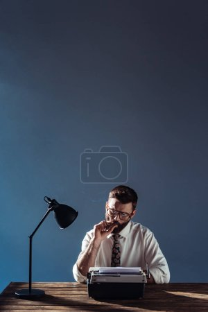 handsome journalist sitting at table with lamp and retro typewriter and smoking on grey background