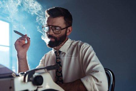 Foto de Reflexivo periodista guapo en copas sentado en mesa con retro máquina de escribir y fumar junto a la ventana - Imagen libre de derechos