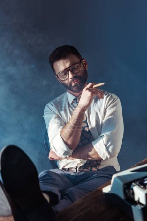 Photo for Bearded journalist with closed eyes putting feet up on table and smoking on grey background - Royalty Free Image