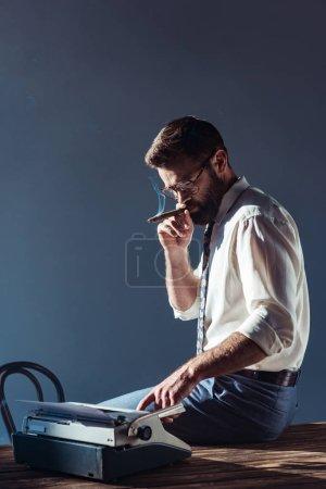 handsome man smoking and using typewriter