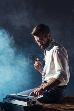 Photo pour Homme beau fumer assis sur table avec machine à écrire - image libre de droit