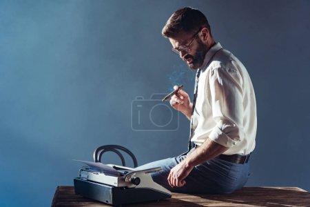 Photo pour Bel homme fumant et en regardant la machine à écrire - image libre de droit