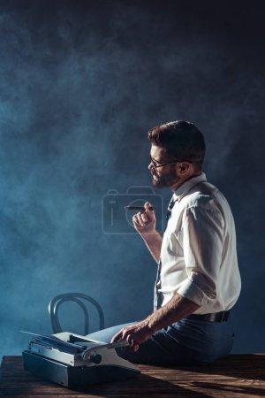 Foto de Hombre guapo fumando y sentado en la mesa con máquina de escribir - Imagen libre de derechos