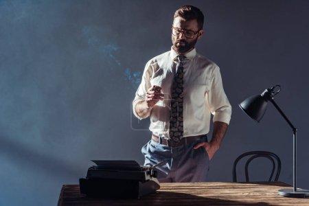 Photo pour Bel homme debout près de table et en regardant de machine à écrire - image libre de droit