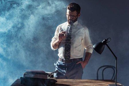 Foto de Guapo hombre barbudo en gafas sosteniendo el cigarro y mirando a la máquina de escribir - Imagen libre de derechos
