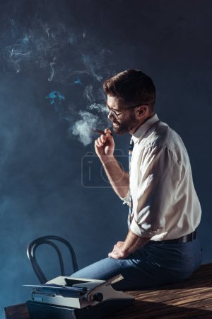 Photo for Handsome bearded man in glasses sitting on table while smoking cigar - Royalty Free Image