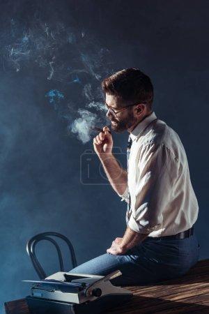 Photo pour Bel homme barbu dans des verres, assis sur la table tout en cigare fumer - image libre de droit