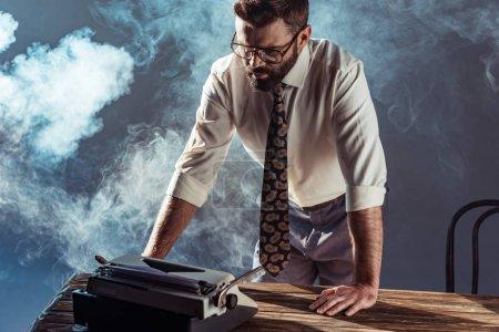 Photo pour Bel homme barbu tenant cigare et regardant à typewriter - image libre de droit