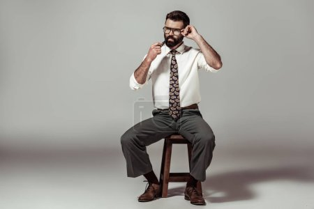 handsome bearded man in glasses sitting on chair and smoking pipe