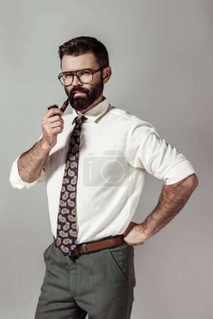 Photo for Handsome bearded man in glasses and shirt smoking pipe and looking at camera isolated on grey - Royalty Free Image